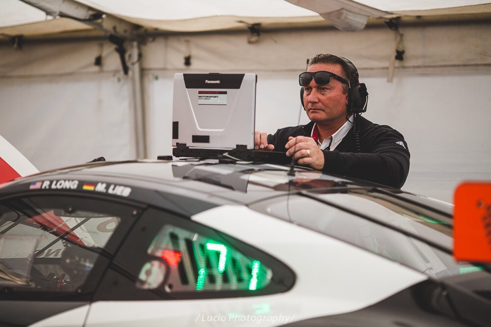 Pirelli world challenge at lime rock park. Crew member tuning Patrick Long's 911 race car.